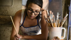 Young female art student mixing paint on palette in art studio with brushes i Stock Footage
