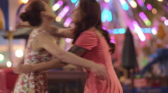 Stock Video Footage of Two friends meet at a carnival and hug