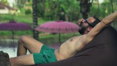 Young man waking up from sleep on bean bag by the pool Stock Footage