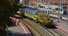Woman at Platform Workers are Walking Two Blue And Yellow Passenger Electric - stock footage