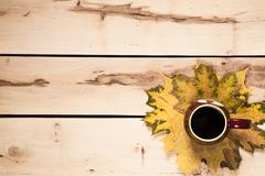 Autumn background. Cup of coffee on the table with leaves - stock photo