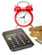 Alarm clock with bills and coins - stock photo