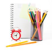 Pencil cup with crayons and copy book - stock photo