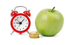 Fresh apple with coins and alarm clock Stock Photos
