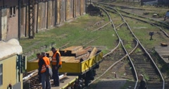 Workers in Orange Workwear Workers on Yellow Locomotive Platphorm with Railroad - stock footage
