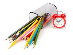 Fallen pencil cup with crayons and red alarm clock - stock photo