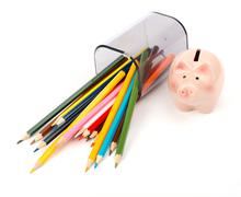 Fallen pencil cup with crayons and pink piggy bank Stock Photos