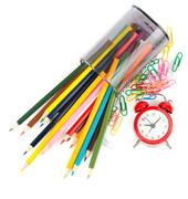 Fallen pencil cup with crayons and alarm clock - stock photo