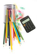 Fallen pencil cup with crayons and calculator Stock Photos