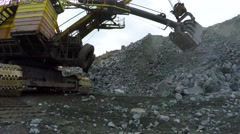 Multi-ton tracked excavator loads ore into the bucket with a screech. - stock footage