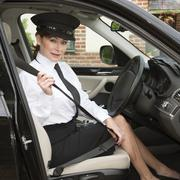 Professional woman driver adjusting her seat belt Stock Photos
