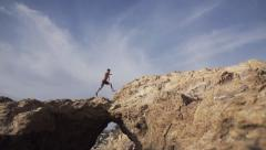 Man Runs Across Natural Rock Arch Way in Slow Motion Stock Footage