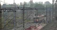 Red Electric Train Moves Away Railroad Tracks And Contact Network Lamp Posts Stock Footage