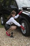 Stock Photo of Woman chauffeur checking tyre pressure and inflating tire