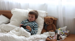 Stock Video Footage of Sick child boy lying in bed with a fever, resting