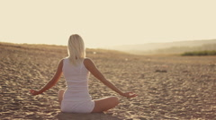 Young beautiful woman doing yoga on the shore of lake Stock Footage