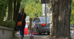 Mom Little Blonde Girl is Riding The Kick Scooter by Street Close Up Woman is Stock Footage