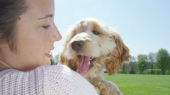 Woman relaxing in the park with cute young cocker-poo puppy. - stock footage