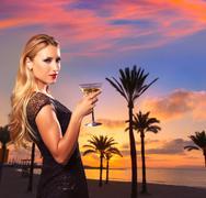 Blond girl sunset Arenal beach drinking vermout Stock Photos