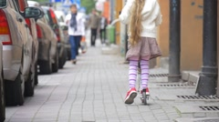 Girl on a Kick Scooter Girl in Skirt With Blonde Hairs is Ridding a Kick - stock footage