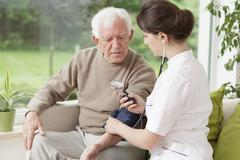 Stock Photo of Young medic taking blood pressure
