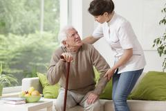 Nurse helping elderly man - stock photo