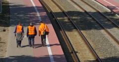 Three Workers Men in Orange Workwear are Walking Away along the Empty Railroad Stock Footage
