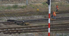 Two Workers Men in Orange Workwear are Walking Fast along the Railroad Checking Stock Footage