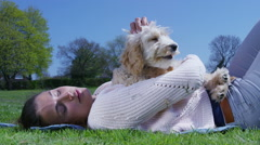 Woman relaxing in the park with cute young cocker-poo puppy. Stock Footage