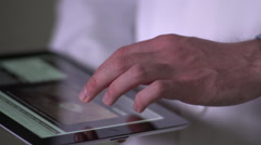 Doctor's hand touching ipad, tight shot, left side - stock footage