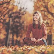 Beautiful happy young woman in the autumn park. Joyful woman is having fun ou - stock photo
