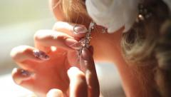 Woman putting on an earring Stock Footage