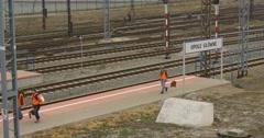 Tree Railroad Workers Women in Orange Workwear Are Walking along Platform Stock Footage