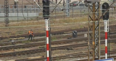 Two Workers in Orange Workwear Are Checking The Railroad Wire Towers Wires Sity - stock footage