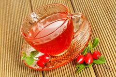 Rose hip tea with fresh berries on the wooden background Stock Photos