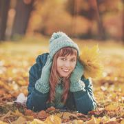 Beautiful happy young woman in the autumn park. Joyful woman wearing bright t - stock photo