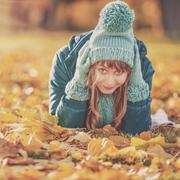 Beautiful happy young woman in the autumn park. Joyful woman wearing bright t Stock Photos