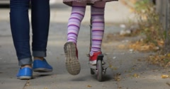 Mom Little Blonde Girl is Riding Kick Scooter by Street Feet Red Sneakers Blue Stock Footage
