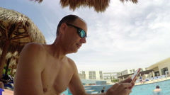 Man checking his smart phone while on vacation at pool side - stock footage