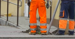 Two Workers Men in Orange Workwear Close Up Are Digging Installing the Stock Footage