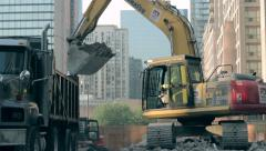 Large Backhoe transfers rubble to dumptruck Stock Footage