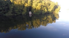 Flight over a lake and mixed forest Stock Footage
