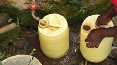 Stock Video Footage of A woman fills a jug with fresh drinking water in Kenya.