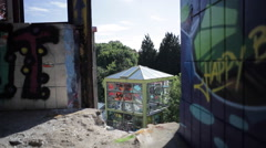 View of broken sun bathing glass house full of graffiti from abandoned tower Stock Footage