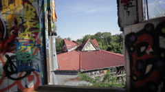 View of broken orange roof of an abandoned building from graffiti tower - stock footage