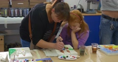 Teacher Woman Helps The Teenage Girl with Red Hairs to Paint Children Are Stock Footage