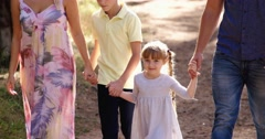 Family holding hands walking over green lawn outdoor park Stock Footage