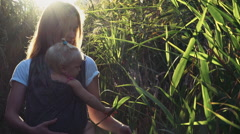 Babywearing, young female carrying a baby in sling Stock Footage