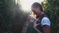 Babywearing, mother carrying a baby in sling Stock Footage
