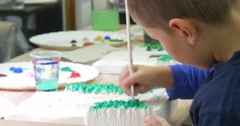 Boy is Painting Attentively with Brush Kids Creating Hand-Made Products for - stock footage